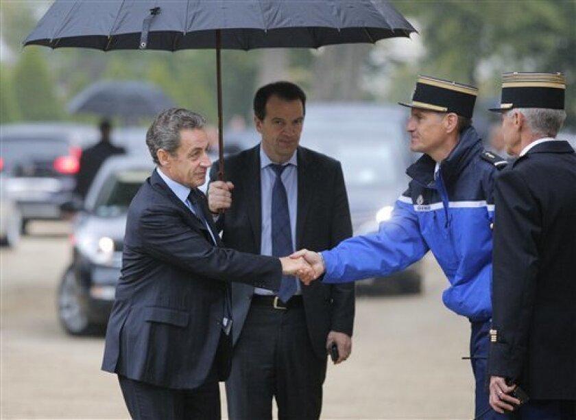 El ex presidente de Francia Nicolas Sarkozy, a la izquierda, estrecha la mano de un gendarme a su llegada para una ceremonia en memoria de las víctimas del terrorismo en París, el lunes 19 de septiembre de 2016.
