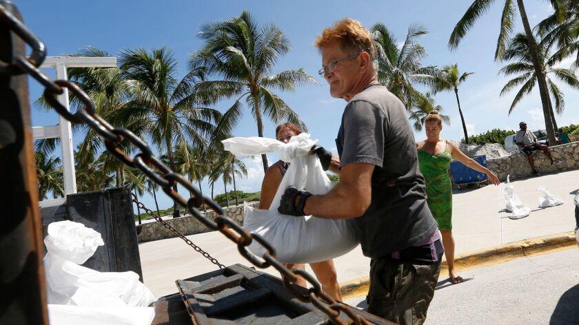 MIAMI, FLORIDA--SEPT. 7, 2017--Genaro Dacosta, age 65, of Miami Beach loads sandbags. He says he can