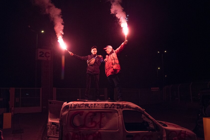 Protesters with flares stand on a vandalized car during a blockade of the port of Marseille in southern France on Thursday.