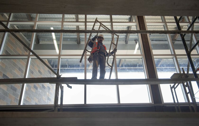 A construction worker removes a piece of scaffolding from inside the new Pacific Trails Middle School classroom building on June 12, 2015 in Carmel Valley.