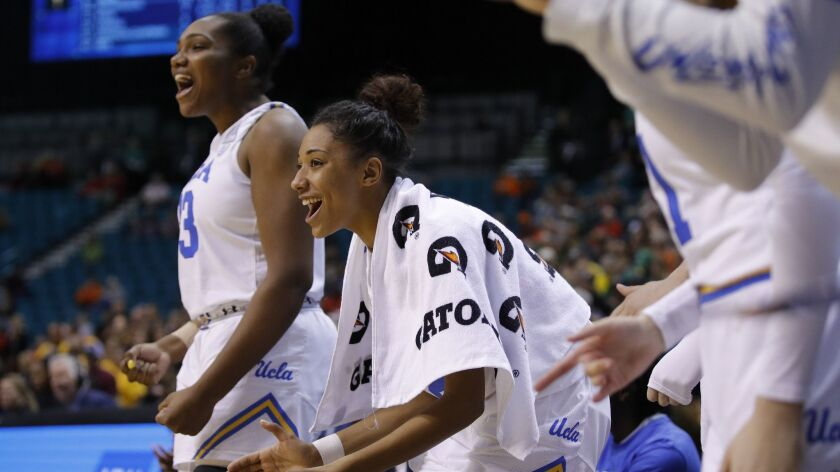 UCLA's Ahlana Smith, center, cheers during the second half of an NCAA college basketball game agains