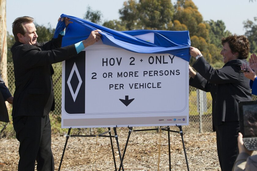 The first phase of the project was building the HOV lane in each direction along an eight-mile portion of I-805 from East Naples Street in Chula Vista to State Route 94 in San Diego.  Unveiling the new sign is Laurie Berman (Caltrans San Diego District Director) and National City Mayor Ron Morrison