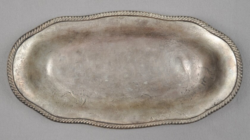 A silver-plated serving platter from the USS San Diego. A number of artifacts have been removed from