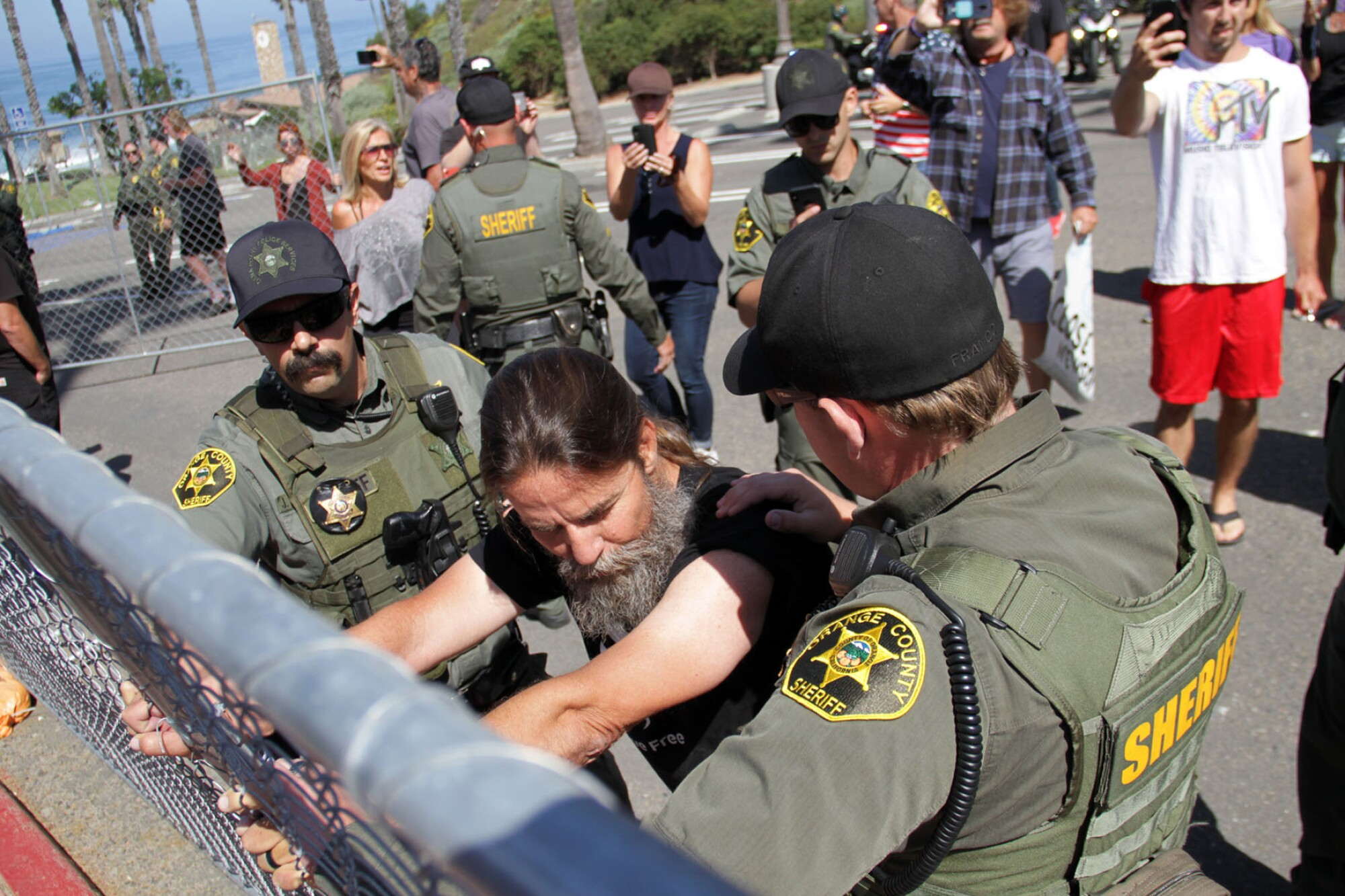 Alan Hostetter grips a fence as sheriff's deputies stand nearby
