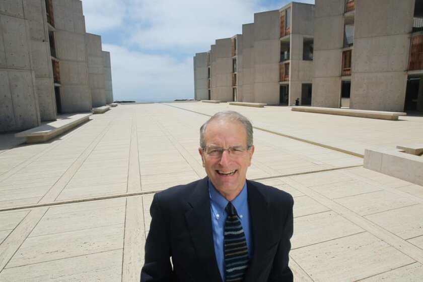 Dr. William Brody, President of the Salk Institute, standing between the facility's main two main research buildings.
