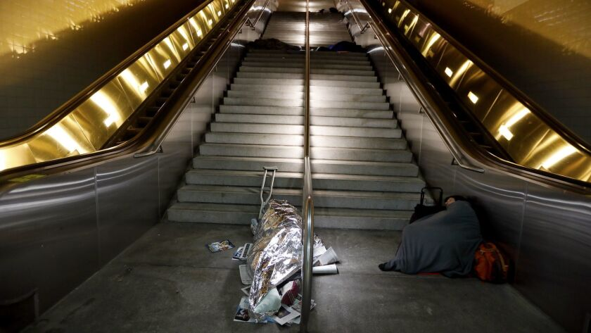 LOS ANGELES, CA MARCH 27, 2018: People sleep on the steps between the escalators at 5:15am at the