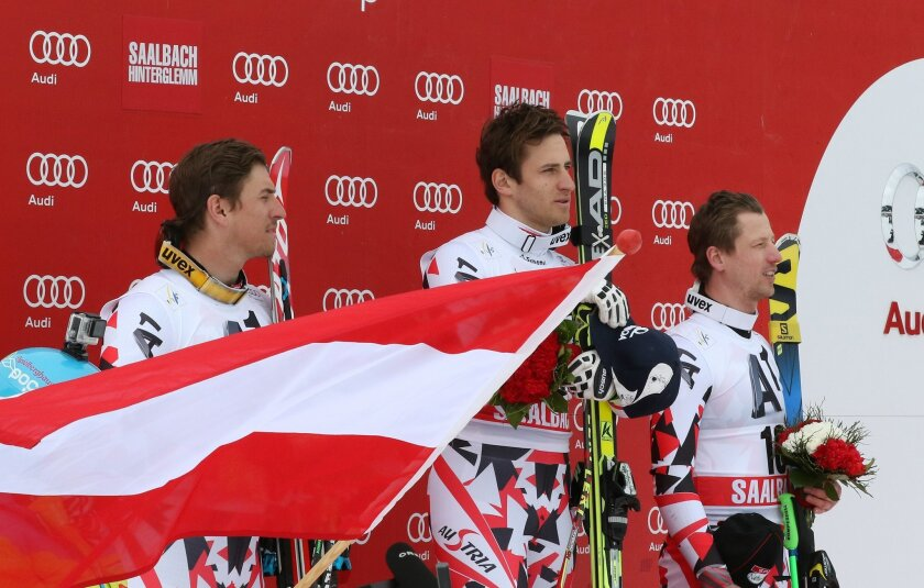From left, Max Franz, of Austria, second placed, Matthias Mayer of Austria, winner, Hannes Reichelt, of Austria, third placed, celebrate on the podium after an alpine ski World Cup men's downhill event, in Saalbach Hinterglemm, Austria, Saturday, Feb. 21, 2015. (AP Photo/Giovanni Auletta)