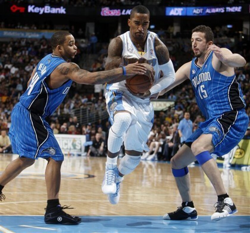 Denver Nuggets guard J.R. Smith, center, drives the lane between Orlando Magic guards Jameer Nelson, left, and Hedo Turkoglu, of Turkey, in the fourth quarter of the Magic's 106-88 victory in an NBA basketball game in Denver on Saturday, Jan. 17, 2009. (AP Photo/David Zalubowski)
