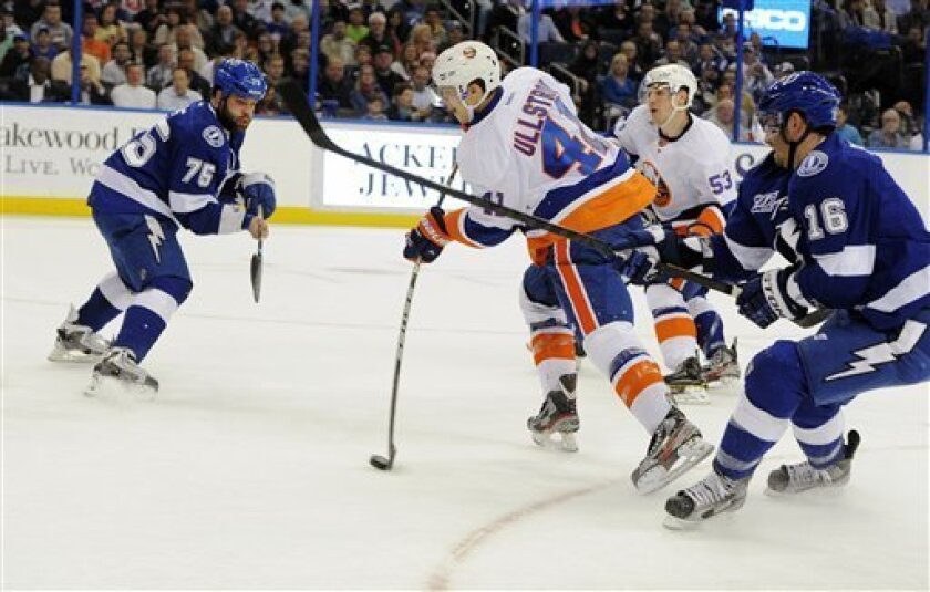 New York Islanders left wing David Ullstrom (41), of Sweden, shoots between Tampa Bay Lightning defenseman Radko Gudas (75), of the Czech Republic, and right wing Teddy Purcell (16) during the first period of an NHL hockey game, Thursday, March 14, 2013, in Tampa, Fla. (AP Photo/Brian Blanco)