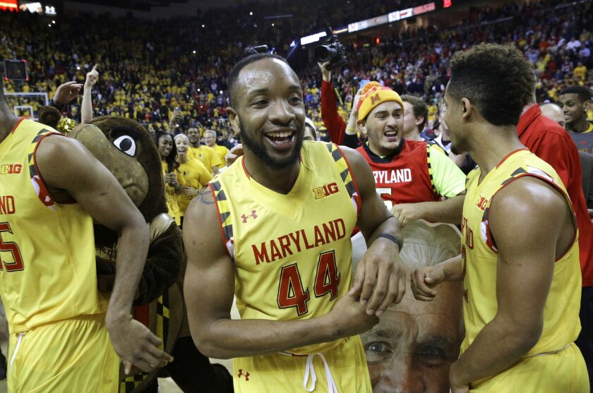 Maryland guard/forward Dez Wells (44) celebrates after fans stormed the court after an NCAA college basketball game against Wisconsin, Tuesday, Feb. 24, 2015, in College Park, Md. Wells contributed a game-high 26 points to Maryland's 59-53 upset win. (AP Photo/Patrick Semansky)