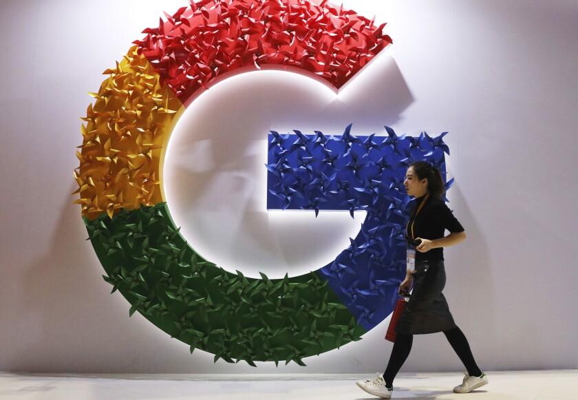 """FILE - In this Monday, Nov. 5, 2018 file photo, a woman walks past the logo for Google at the China International Import Expo in Shanghai. France's anti-competition watchdog has decided to fine Google 220 million euros ($268 million) for abusing its """"dominant position"""" in the complex business of online advertising. It said Monday, June 7, 2021 that the move is unprecedented. (AP Photo/Ng Han Guan, File)"""