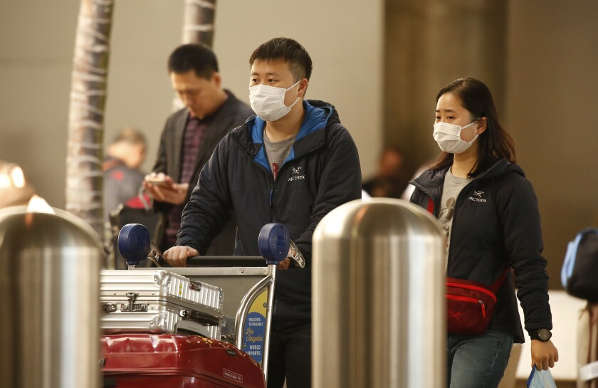 Travelers wear masks at the Tom Bradley International Terminal at Los Angeles International Airport in January.