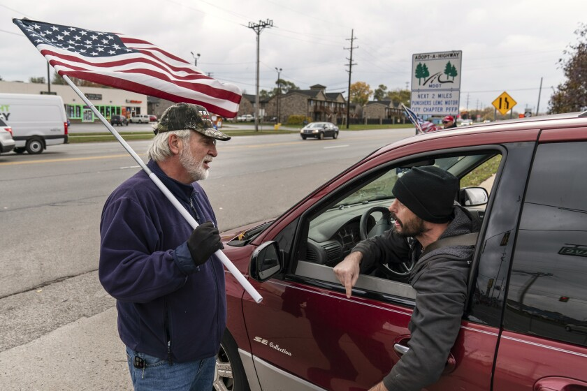A passing motorist at right argues with Trump supporter Mike Jamerson, left, during a rally.