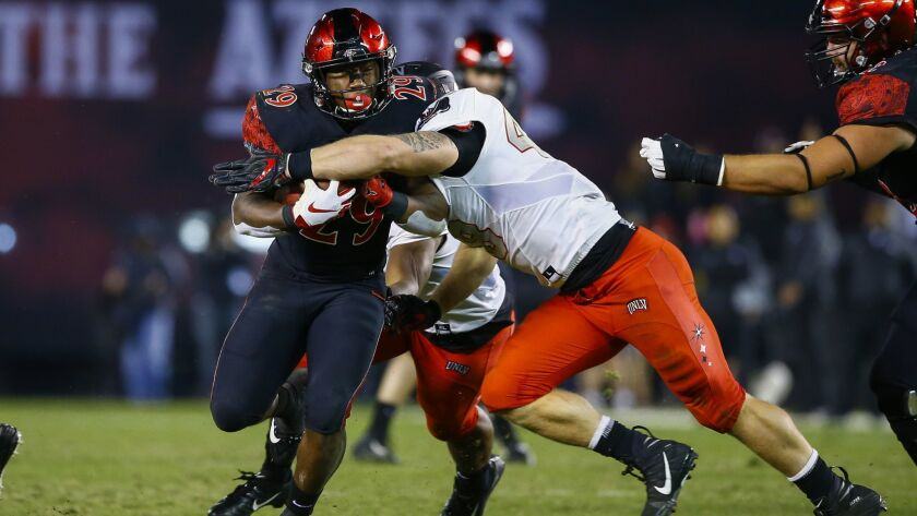 SDSU running back Juwan Washington (29) is tackled by UNLV linebacker Bailey Laolagi (48) in the third quarter.