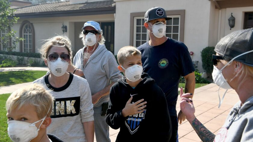Members of the Cash family wear masks after returning to their Westlake Village neighborhood on Friday after evacuating from the Woolsey fire.