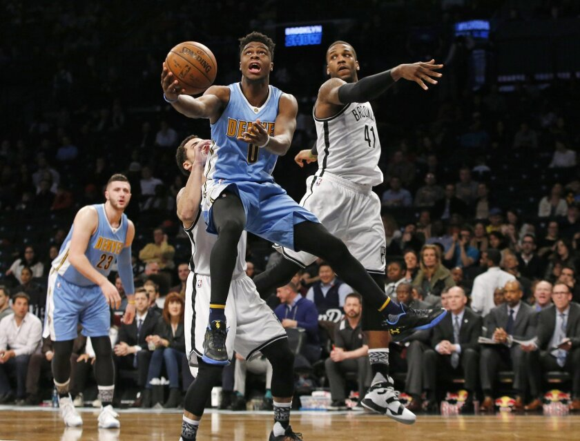 Denver Nuggets guard Emmanuel Mudiay (0) backs into Brooklyn Nets guard Shane Larkin (0) as he goes up for a lay-up with Nets forward Thomas Robinson (41) defending in the first half of an NBA basketball game, Monday, Feb. 8, 2016, in New York. (AP Photo/Kathy Willens)