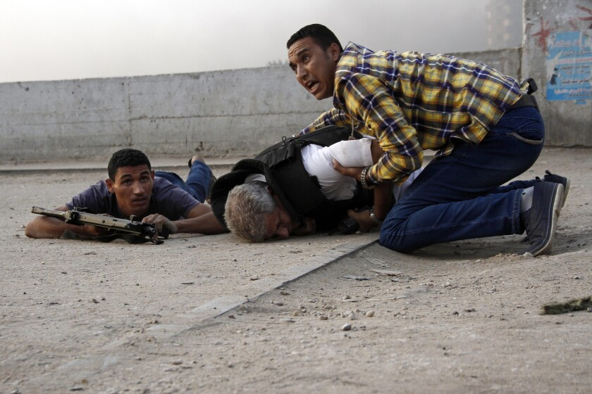 Egyptian security forces try to help Giza Police Gen. Nabil Farrag, center, who was killed when militants opened fire on security forces deployed to Kerdasa to drive off suspected Islamists taking control of the town near the Giza Pyramids on Sept. 19, 2013.
