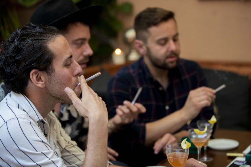Three men smoking joints.