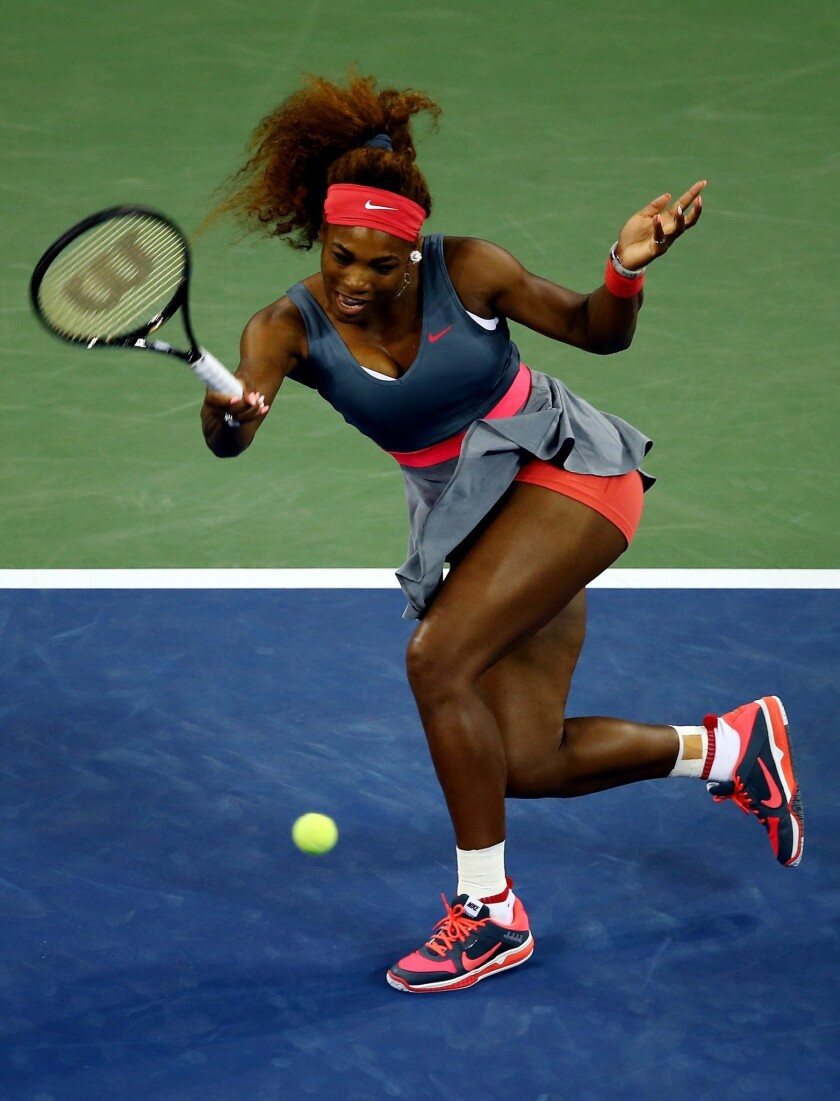 Serena Williams returns a shot during her first-round victory over Francesca Schiavone at the U.S. Open on Monday.