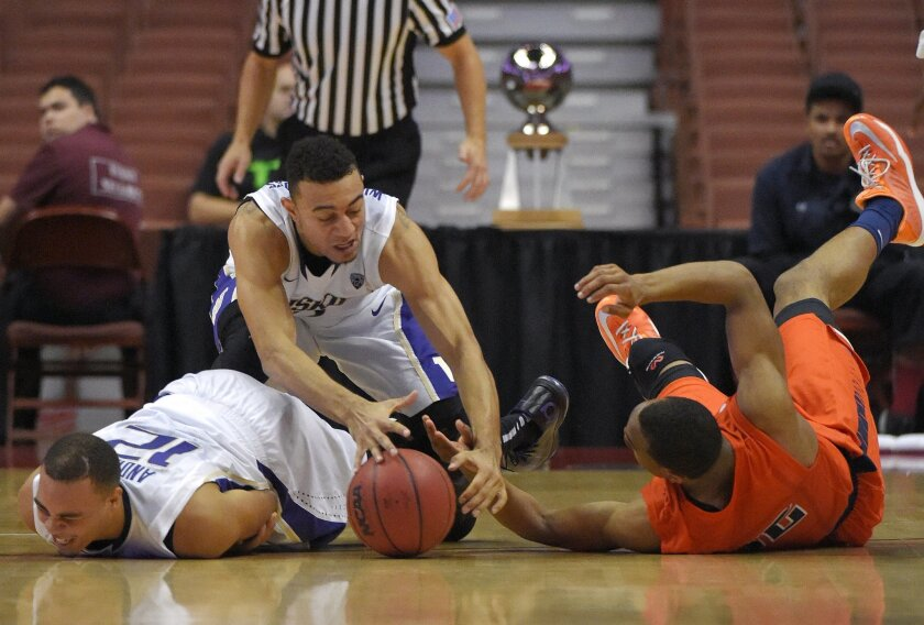 Washington guard Nigel Williams-Goss, center, battles for a loose ball with UTEP forward Vince Hunter, right, as they fall over guard Andrew Andrews during the second half an NCAA college basketball game at the the Wooden Legacy tournament, Sunday, Nov. 30, 2014, in Anaheim, Calif. Washington won 68-65. (AP Photo/Mark J. Terrill)
