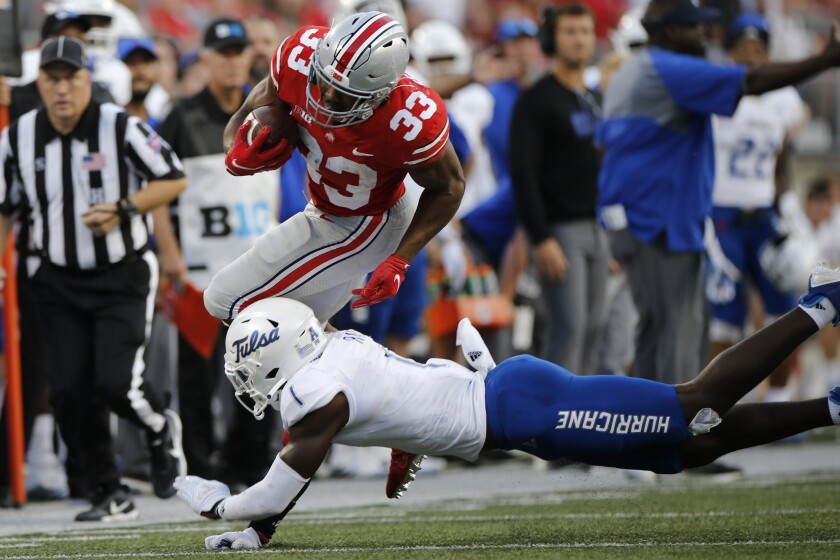 Ohio State running back Master Teague (33) tries to run past Tulsa defensive back Kendarin Ray during the second half of an NCAA college football game Saturday, Sept. 18, 2021, in Columbus, Ohio. (AP Photo/Jay LaPrete)