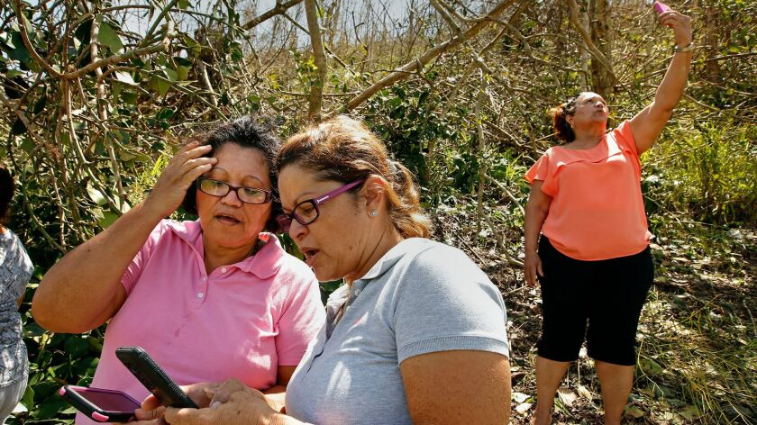People from all over Puerto Rico are heading for the island's hills to try to find a mobile phone signal to notify their family members that they are OK.