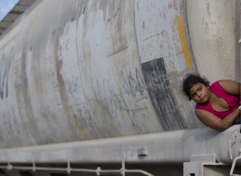 FILE - In this July 12, 2014, file photo, a young migrant girl waits for a freight train to depart on her way to the U.S. border, in Ixtepec, Mexico. According to a report by Human Rights Watch released Thursday, March 31, 2016, Mexico does not comply with its own laws on handling unaccompanied child migrants who arrive in the country fleeing violence in Central America. (AP Photo/Eduardo Verdugo, File)