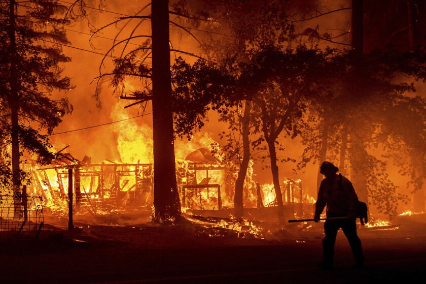 Scorched cars are seen in a clearing in the Indian Falls community of Plumas County, Calif.