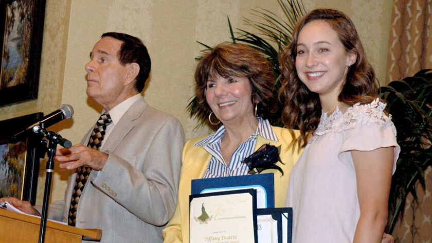 Art and Paul Devine, left, presented a scholarship to Tiffany Duarte who is studying to become a pediatric neurologist.