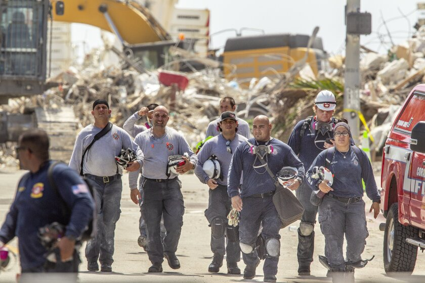 Rescuers walk away from the rubble of the Champlain Towers South collapse, during a shift change, in Surfside, Fla. on Thursday, July 8, 2021. Rescue workers now focused on finding remains instead of survivors in the rubble of the Florida condominium collapse vowed to keep up their search for victims until they cleared all the debris at the site. (Pedro Portal/Miami Herald via AP)