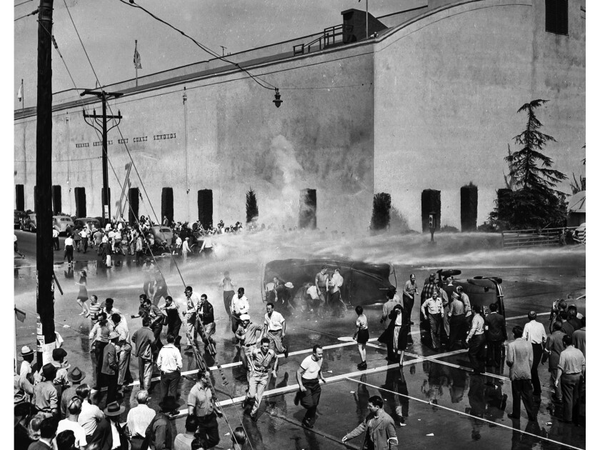 Oct. 5, 1945: Strikers outside Warner Bros. Studios in Burbank scatter and others take cover behind overturned cars as studio firefighters turn hoses on the strikers.