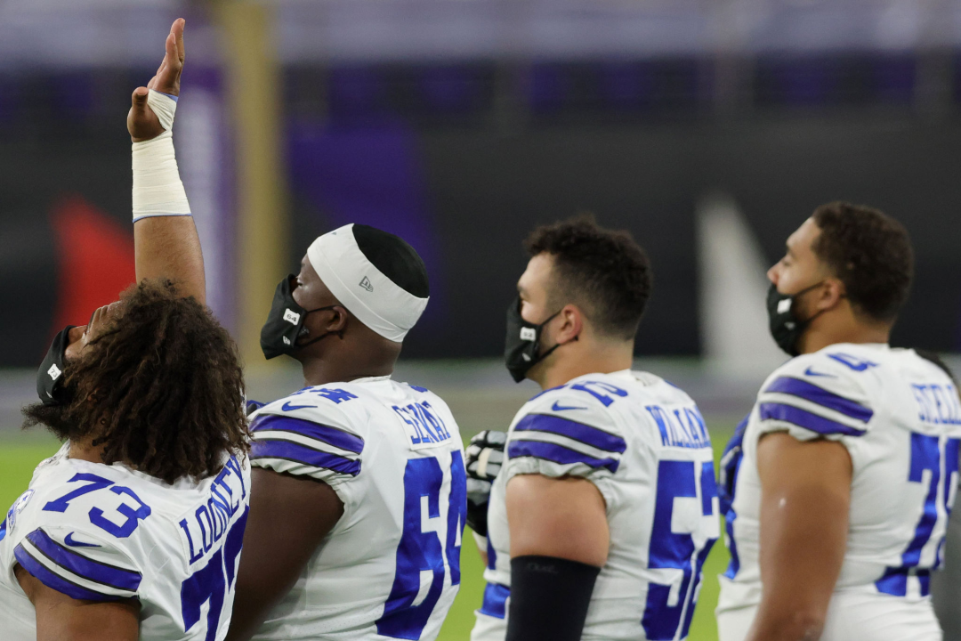 Dallas Cowboys center Joe Looney raises his hand into the air during the national anthem.
