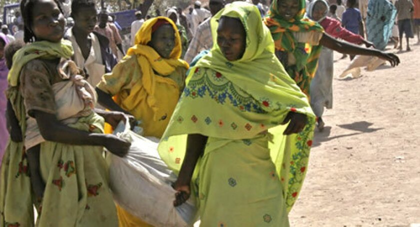 This photo taken February 12, 2008 shows Sudanese women carrying sacks of relief food in Boro Medina, in south Sudan, some of which is instead sold at local markets for meat and other staples.