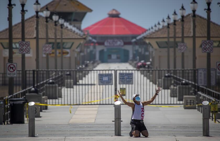 Woman kneels in prayer in front of closed Huntington Beach Pier