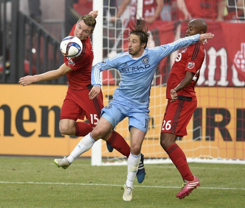 Toronto FC's Eriq Zavaleta (15) and teammate Collen Warner (26) battle against New York City FC's Ned Grabavoy (11) during second-half MLS soccer game action in Toronto, Saturday, June 20, 2015. (Frank Gunn/The Canadian Press via AP) MANDATORY CREDIT