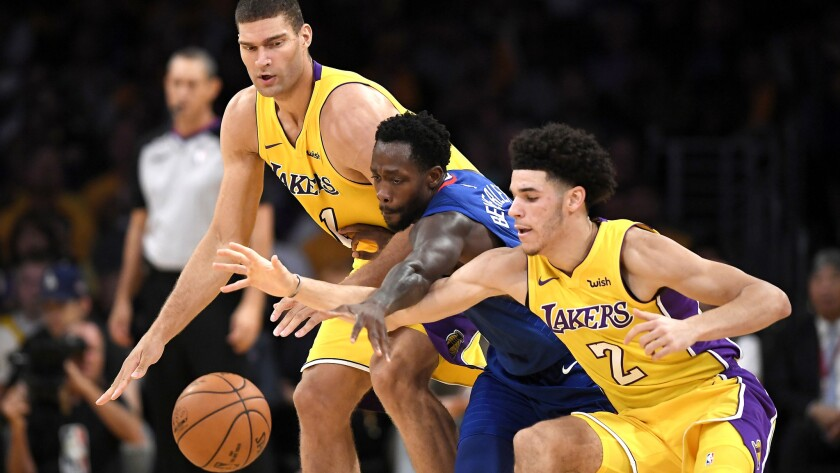 Clippers guard Patrick Beverley fights for a loose ball against Lakers center Brook Lopez, left, and guard Lonzo Ball during the first half Thursday.