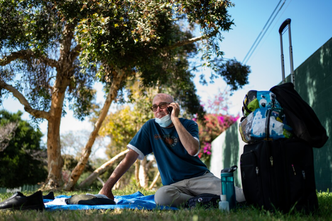 Terrance Whitten takes a phone call while resting in the shade of a tree at Pan Pacific Park in May.
