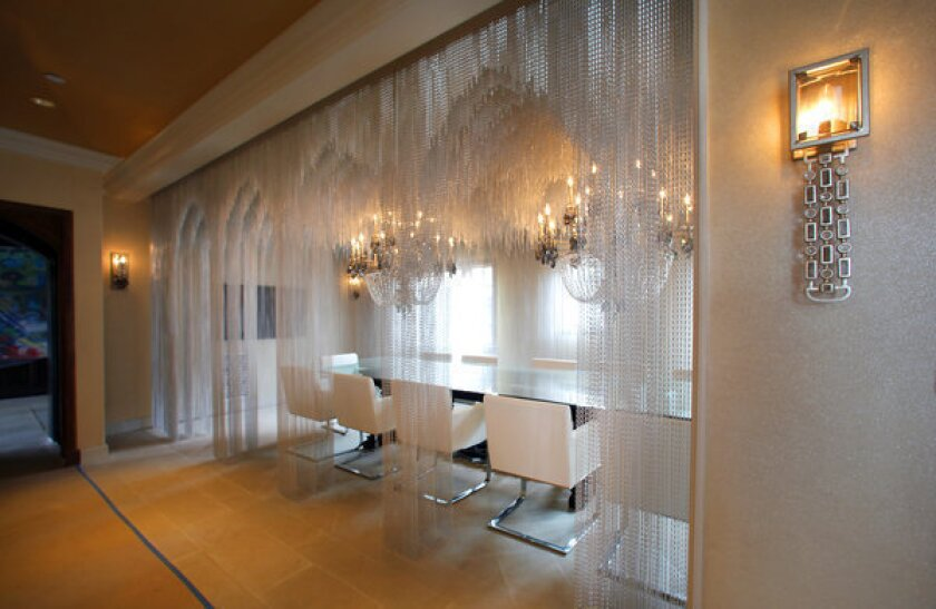 David Bromstad designed the dining room with crystal chandeliers and chains cut in the form of arches. The sconce in the foreground is the Paparazzi by Corbett Lighting.