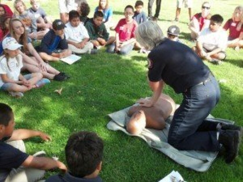 Kids Korps campers learning CPR from Rancho Santa Fe Fire Department Instructor Mary Murphy.