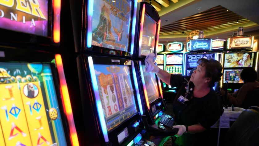 Irma Lopez from Sycuan Casino in El Cajon, cleans one of the slot machines with disinfectant. San Diego casinos are among social centers across the region working to keep patrons safe during a particularly-deadly flu season.