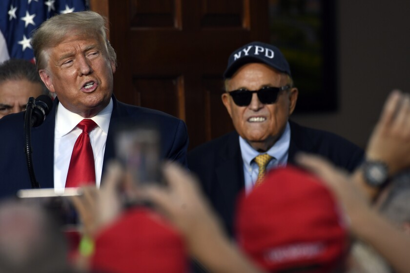 President Donald Trump speaks as Rudy Giuliani, an attorney for President Donald Trump watches, during an event Trump National Golf Club, Friday, Aug. 14, 2020, in Bedminster, N.J., with members of the City of New York Police Department Benevolent Association. (AP Photo/Susan Walsh)