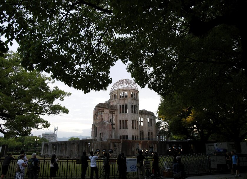 People gather around the gutted Atomic Bomb Dome at the Hiroshima Peace Memorial Park in Hiroshima, southwestern Japan, Thursday, May 26, 2016. President Barack Obama is to visit Hiroshima on Friday, May 27. Seven years ago, a new American president stood before cheering throngs in Prague's histori