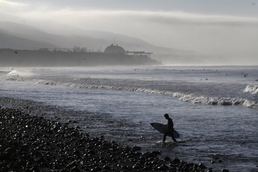 Early morning surfers catch a few waves with the San Onofre nuclear power plant in the background.