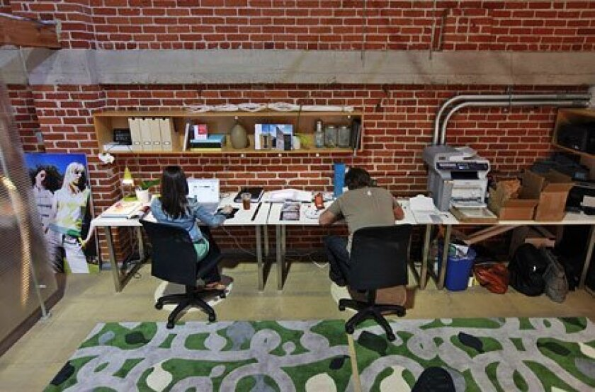 Lexi Campanis (left), who runs a graphic design company, and Josh Skversky handled projects in a 580-square-foot space at HiveHaus on 11th Avenue. (John R. McCutchen / U-T)