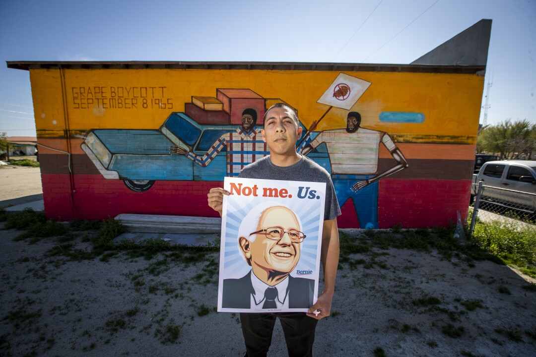 Indio Councilman Oscar Ortiz, 31, holds a sign at the Coachellla Valley's Bernie Sanders campaign headquarters, where he serves as the field organizer.
