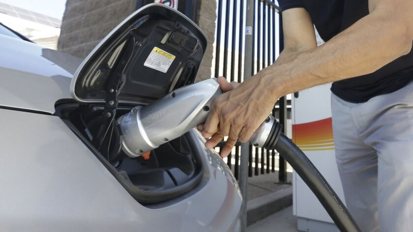 A man plugs a charger into his electric vehicle.