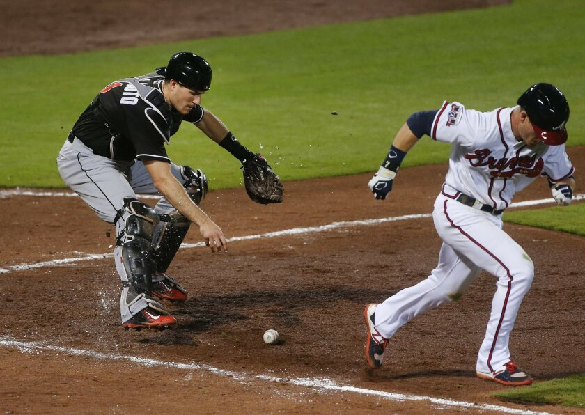 Miami Marlins catcher J.T. Realmuto, left, fields a bunt by Atlanta Braves' Gordon Beckham, right, before throwing to third for the out in the eighth inning of a baseball game Friday, May 27, 2016, in Atlanta. (AP Photo/John Bazemore)