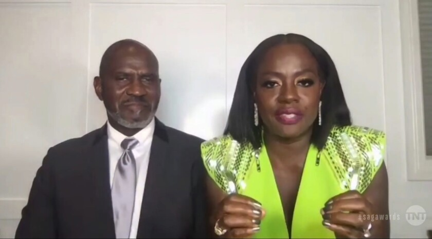 """In this video grab provided by the SAG Awards, Viola Davis, right, accepts the award for outstanding performance by a female actor in a leading role for """"Ma Rainey's Black Bottom,"""" as her husband Julius Tennon looks on during the 27th annual Screen Actors Guild Awards on April 4, 2021. (SAG Awards via AP)"""