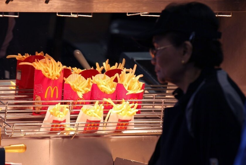 Despite people's best efforts to lose weight by willpower alone, humans are hard-wired to eat as much as possible. Above, McDonald's french fries sit under a heat lamp.