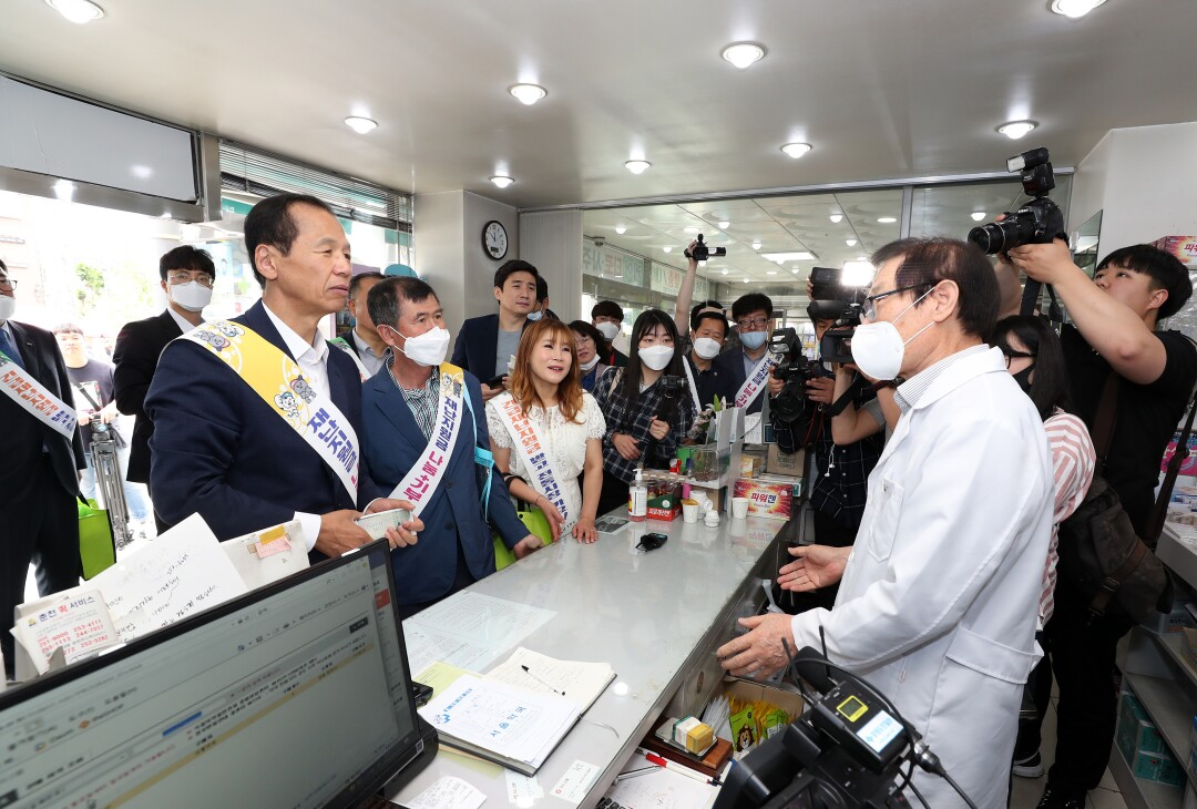 Gov. Choi Moon-soon, left, spends his stimulus money at the pharmacy of Lee Jong-ho, right.